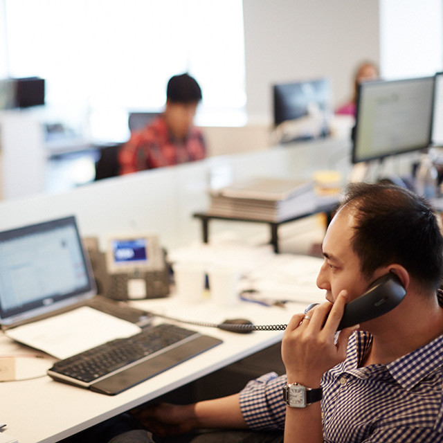 Man talking on the phone while sitting at his work space.
